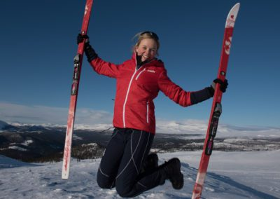 Smiling woman jumps and holds skis
